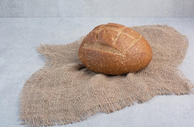 Домашний ржаной хлеб на мешковине на мраморной предпосылке. фото высокого качества