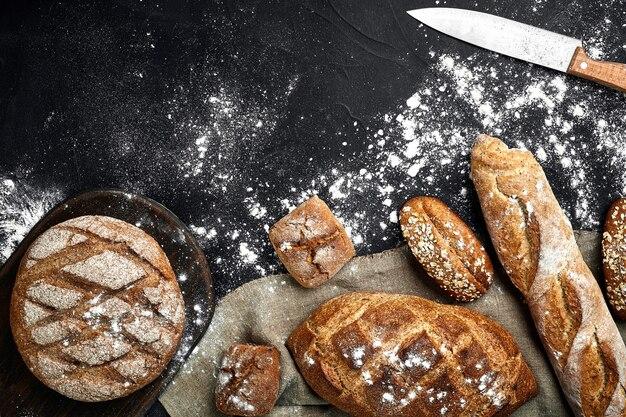 Домашний ржаной хлеб, посыпанный мукой и различными зернами и семенами на черном фоне с шипами ...