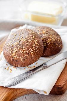 아마씨, 참깨 및 나무 보드에 흰 양귀비 씨앗으로 만든 호밀 빵