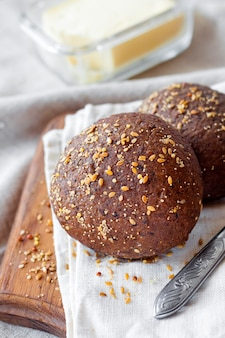 Homemade rye buns with linseeds, sesame and white poppy seeds on wooden board