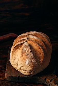 暗い木製のテーブルの上にナイフでまな板に自家製ライ麦パン。