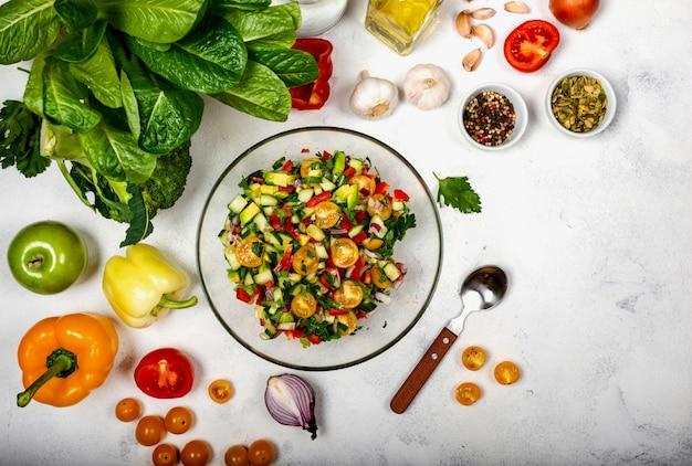 食材とスパイスが入ったガラスのボウルにさまざまな有機野菜を使った自家製サラダ