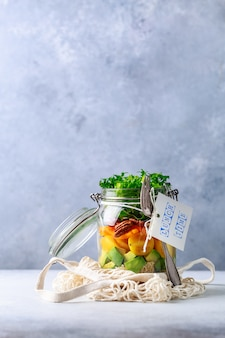 Homemade salad in glass jar with quinoa and vegetables with label lunch time no plastic and take away concept