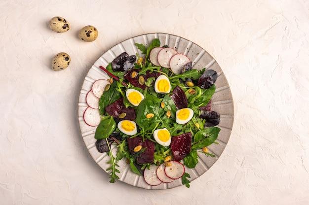 ウズラの卵、ゆでビーツ、大根、ルッコラ、バジルの自家製サラダ、明るい背景にオリーブオイル、コピースペース