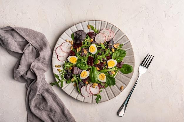 ウズラの卵、ゆでビーツ、大根、ルッコラ、バジルの自家製サラダ、オリーブオイル添え、明るい背景、上面図、コピースペースにリネンナプキンとフォークを添えて