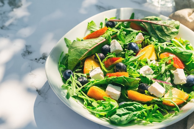 Homemade salad with nectarines blueberries arugula and feta cheese on white marble background