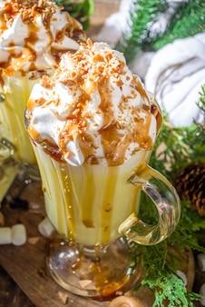 自家製塩キャラメルエッグノッグまたはホワイトホットチョコレートドリンク、キャラメルソース、ホイップクリーム、マシュマロ、木製の背景にクリスマスの冬の装飾のコピースペース