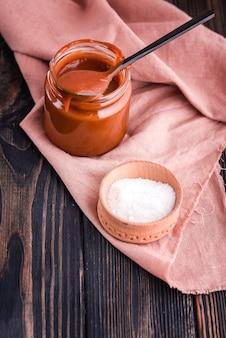 黒いテーブルに自家製の塩キャラメルと美しい黒いスプーンと牛乳。