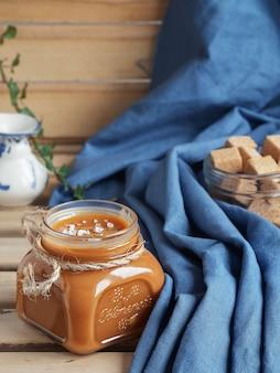 Домашний соленый карамельный соус в стеклянной банке на деревенский деревянный столик. крупный план. пряники