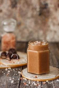 Домашний соленый карамельный соус в банке на винтажном фоне