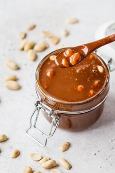 Homemade salted caramel with nuts in glass jar, copy space. ingredient for cake snickers.