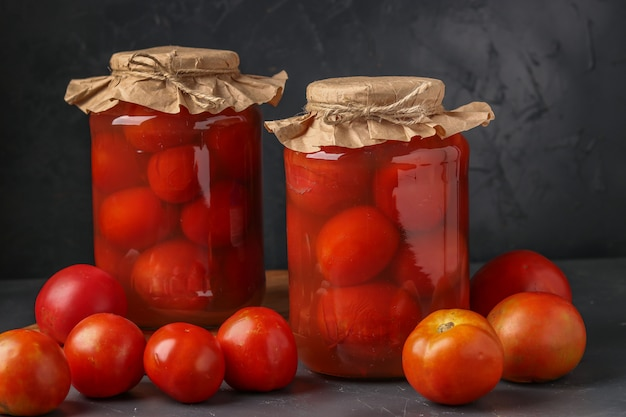 Homemade salted tomatoes in jars on a dark table