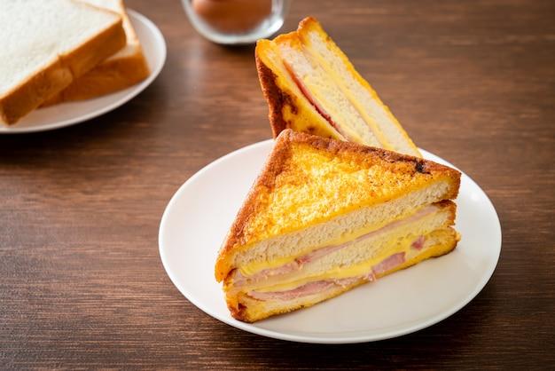Домашний бутерброд с ветчиной и сыром на белой тарелке