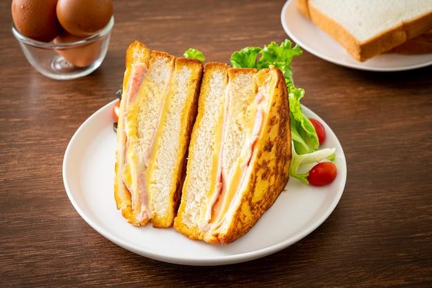 Домашний бутерброд с ветчиной, сыром и салатом на белой тарелке