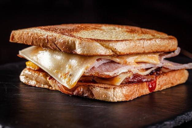 토스트 빵, 돈까스, 베이컨, 체다 치즈, 케첩 소스로 만든 수제 샌드위치. 검정색 배경에 검은 슬레이트에 샌드위치.