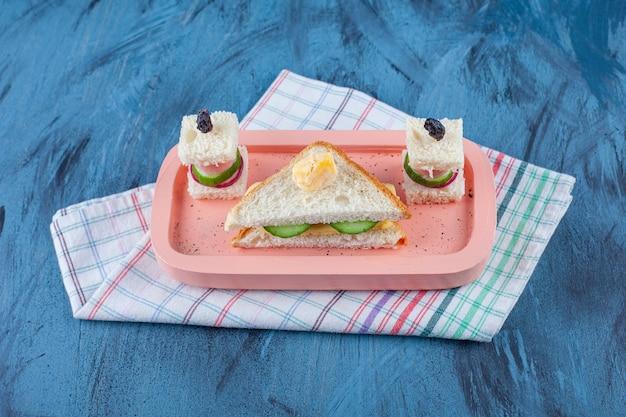 파란색 표면에 차 수건에 보드에 샌드위치 꼬치 옆에 만든 샌드위치.
