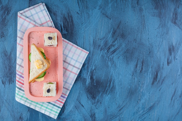 Homemade sandwich next to sandwiches skewer on a board on tea towel , on the blue.