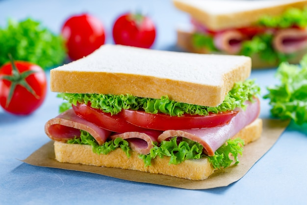 Homemade sandwich with ham, toast bread and fresh vegetables close up on blue surfce
