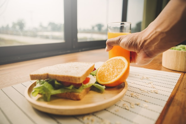 Homemade sandwich with orange juice on wood table