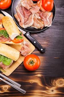 Домашние бутерброды на деревянной доске в окружении ингредиентов, из которых он был сделан