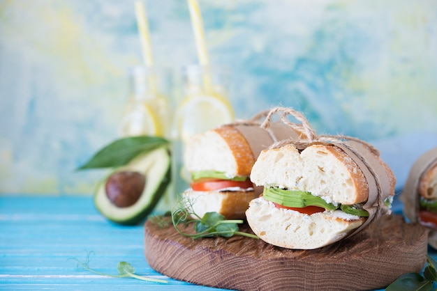 Homemade sandwiches with baguette, avocado and tomatoes on a wooden space