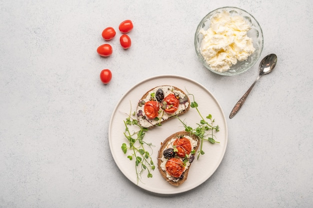 Homemade sandwiches with baked tomatoes, olives, cheese and herbs on bread on a white ceramic plate