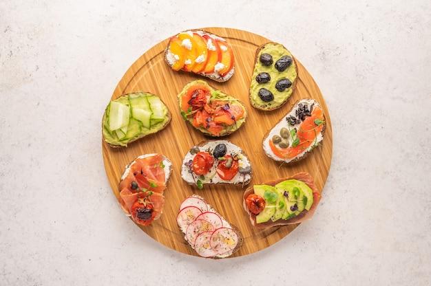 Домашние бутерброды с хлебом и различными ингредиентами и специями на светлом месте. здоровая вкусная еда на завтрак и обед
