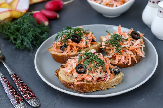 Homemade sandwiches with carrots and radishes, decorated with boiled egg and black olives in a plate against a dark