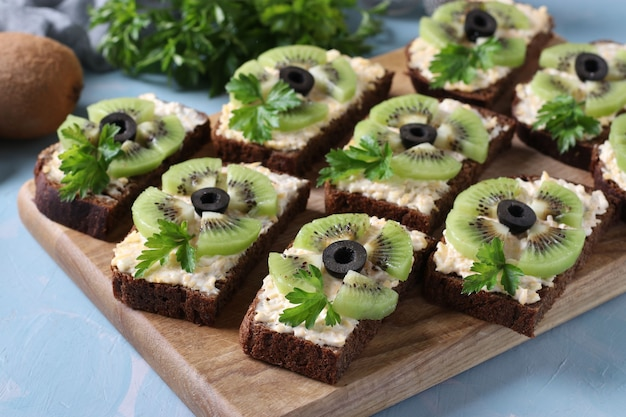 Homemade sandwiches with kiwi, cheese, garlic and black olives on wooden board on light blue background. closeup