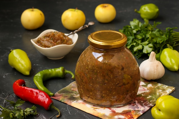 Homemade sauce adjika with hot pepper, garlic, apples, parsley and dill in a jar on a dark wall