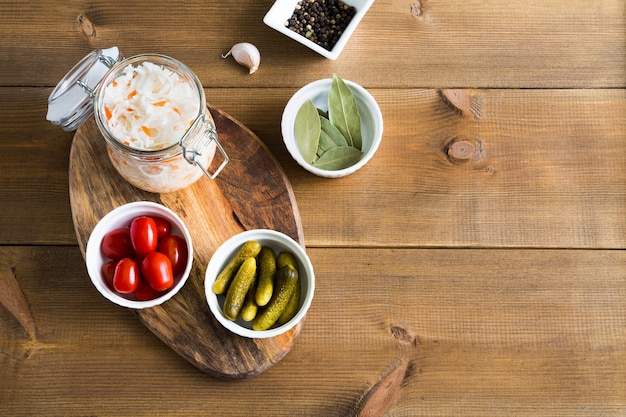 Homemade sauerkraut in glass jar and bowls with marinated cucumbers and tomatoes flat lay on wooden background with copy space.