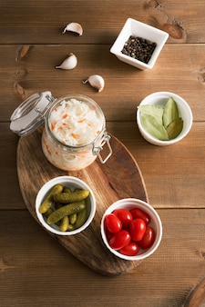 Homemade sauerkraut in glass jar with pickled vegetables flat lay on wood