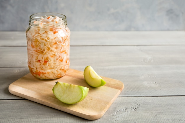 Homemade sauerkraut in glass jar on wooden, white background. next to it are slices of apple. fermented food. close up, copy space composition.