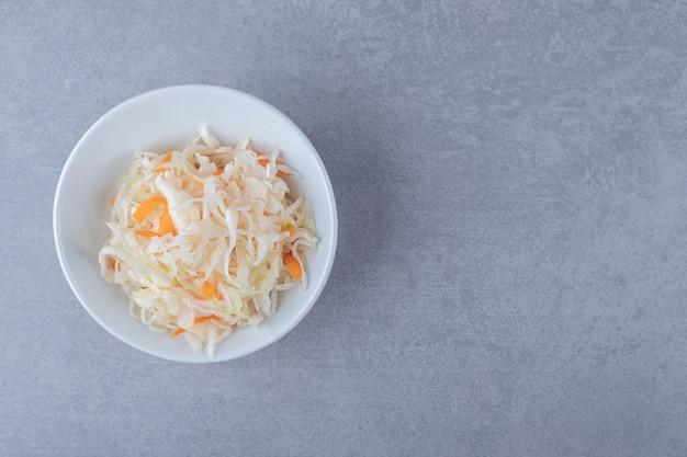 대리석 배경에 그릇에 홈메이드 소금에 절인 양배추.