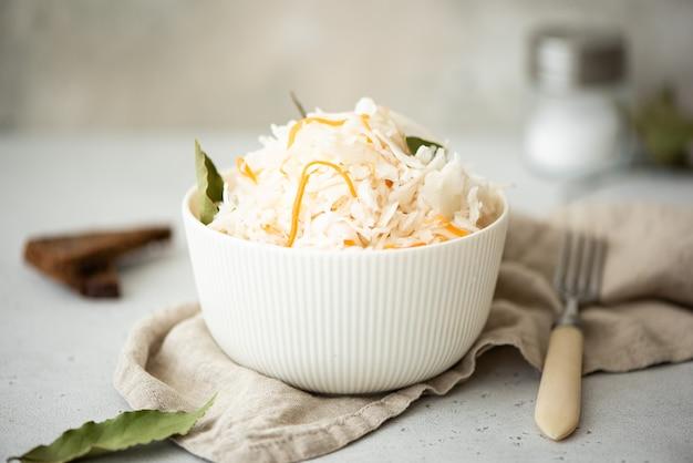 흰 그릇에 당근과 베이 잎으로 만든 소금에 절인 양배추