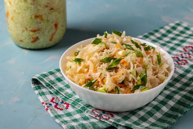 Homemade sauerkraut with carrots and green onions in a bowl on a light blue background, fermented food, top view, flat lay