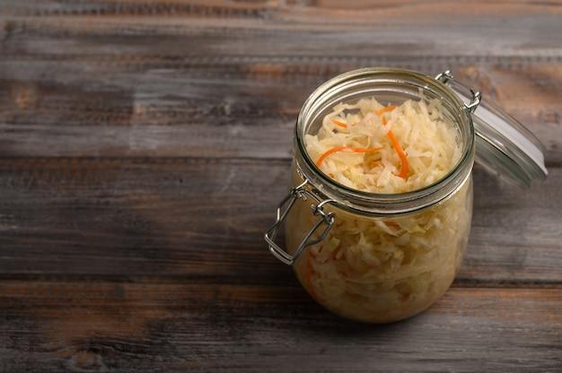 나무 갈색 테이블에 열린 뚜껑이있는 유리 항아리에 당근으로 만든 소금에 절인 양배추. 확대. 공간 복사