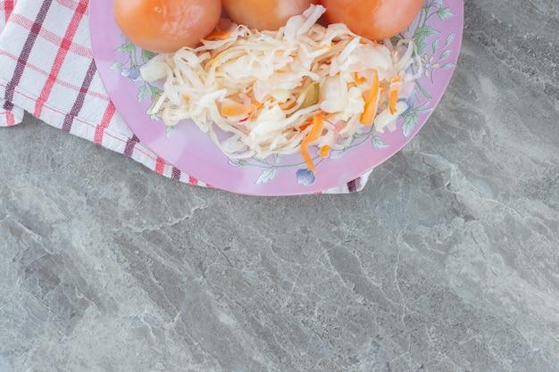 Домашняя квашеная капуста с помидорами на розовой тарелке. вид сверху.
