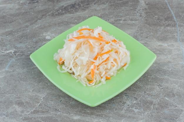 Crauti fatti in casa sul piatto giallo su sfondo grigio.