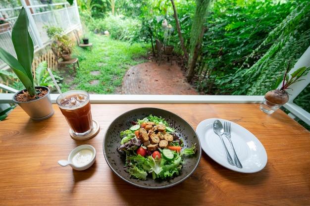 木製のテーブルに新鮮な野菜、トマト、アメリカーノコーヒーを添えた自家製ソーセージサラダ