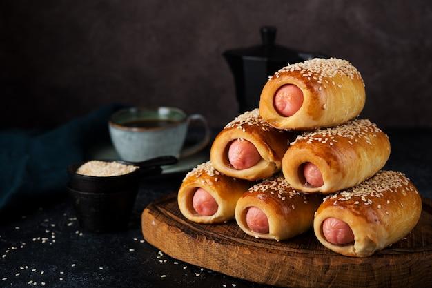 Домашние колбаски, запеченные в тесте (свиньи в одеялах), фаст-стрит фуд, крупный план