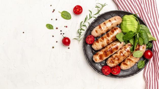 Домашние колбаски из курицы индейки, обжаренной со шпинатом, авокадо и помидорами черри. кето палеодиета. формат длинного баннера. вид сверху.