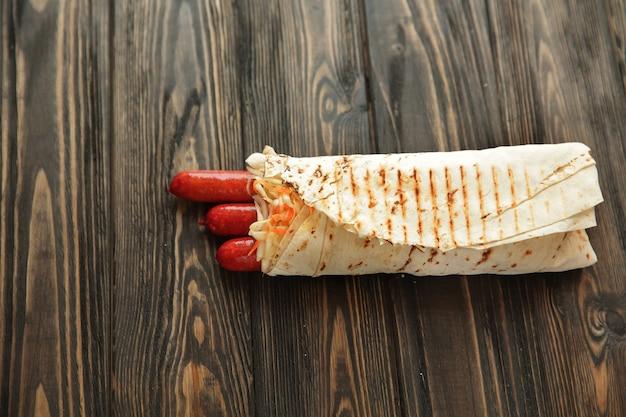 복사 공간이 있는 나무 background.photo에 있는 피타 빵으로 만든 수제 소시지.