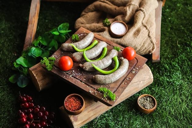 Домашние колбаски на деревянной доске с мясом помидор зелень соль перец вид сбоку