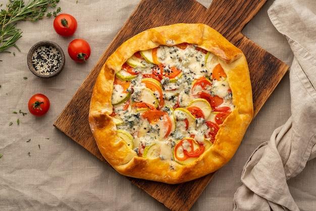 Домашний пикантный галет с овощами, пшеничный пирог с помидорами, цукини, голубой сыр горгонзола. кростата в деревенском стиле на темной льняной текстильной скатерти.