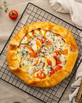 Домашний пикантный галет с овощами, пшеничный пирог с помидорами, цукини, голубой сыр горгонзола. кростата в деревенском стиле на сетке на темной льняной текстильной скатерти.