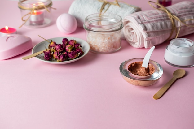 Homemade scrub and skin care with natural organic ingredients on pink background with towels, candles and soap