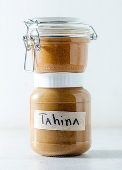 Homemade sesame seed tahini spread sauce in a sealed jar on the table