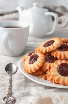 丸い形の自家製ショートブレッドクッキー。りんごジャムのフィリングをトッピング。白いお皿に。背景グレーのリネン。背景には白いティーポットとカップがあります。カントリースタイル