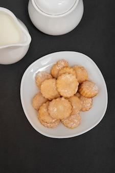 Домашнее песочное печенье на белой тарелке, вид сверху. выпечка к чаю